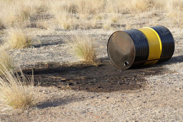 A tipped oil barrel spills its contents onto the soil in an open field.